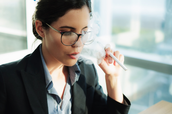 Stressed female executive vaping at work